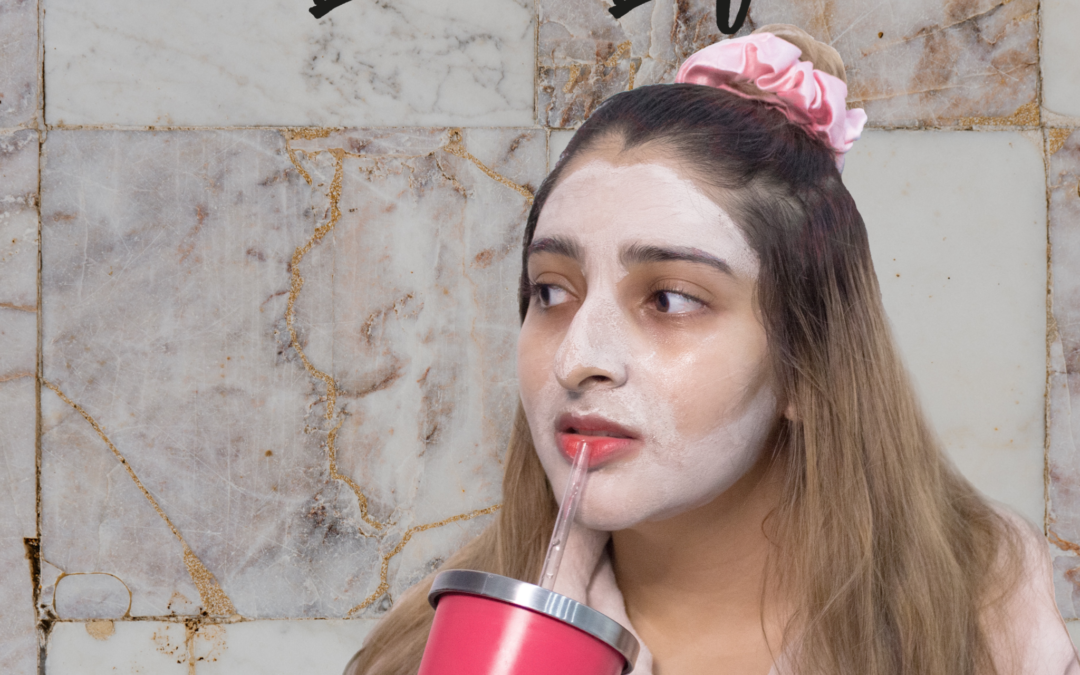 model wearing a skincare mask holding a cup